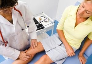врач ощупывает колено пациентки