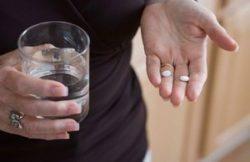 таблетки и стакан воды в руках женщины