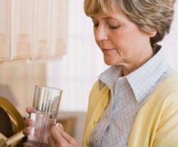 женщина принимает таблетки, чтобы устранить боль в пояснице