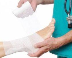 врач бинтует ногу пациента