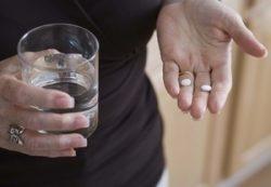 две таблетки в руках женщины