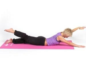 женщина на коврике выполняет упражнения