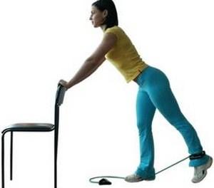 девушка держится за стул и выполняет упражнение ногой