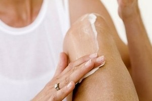женщина наносит лекарство на колено
