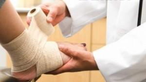 врач обматывает ногу пациента эластичным бинтом