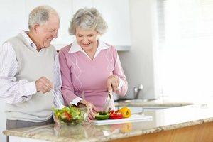 пожилые люди готовят салат